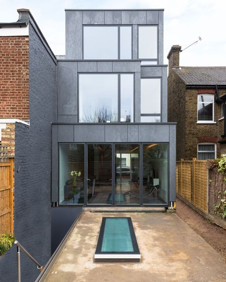 The rear facade is clad in charcoal Cembonit and peppered with windows