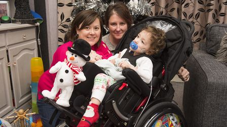 Cohen Messenger in his new wheelchair with his parents Aimee and Kirstie Messenger.Picture: Nick But