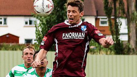 Wingate & Finchley centre-back Sean Cronin leaps to head the ball clear. Picture: David Stevens