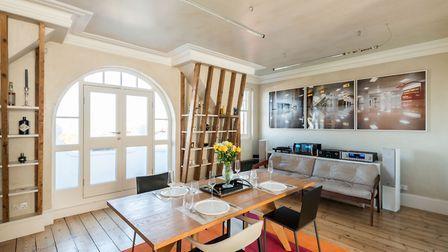 The open plan living space makes use of exposed woodwork by using it as additional storage space