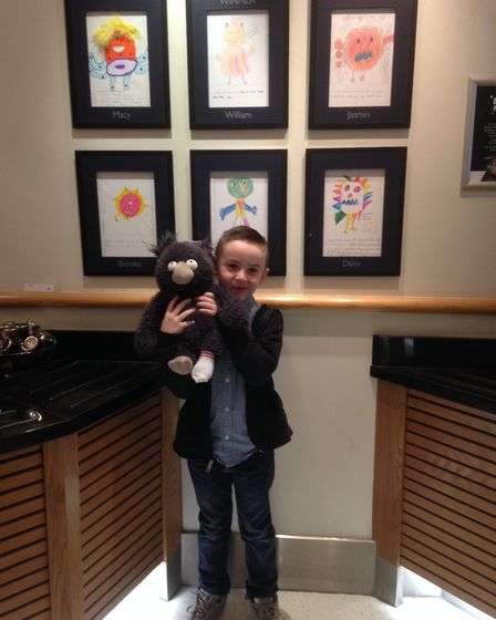 William F is pictured in front of his winning design at the John Lewis store in Norwich with his pri