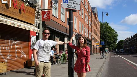 Bridget Burrows pointing at the misleading parking bay sign with her boyfriend Alastair Mason. Pictu