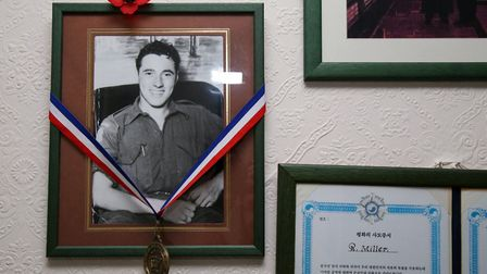 Certificates and photos of his time in the war hanging in Ron Miller's living room, decorated with a