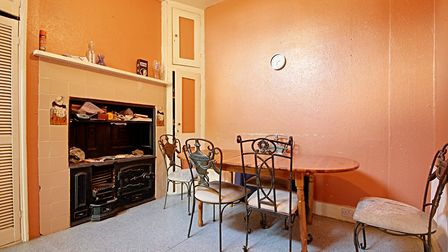 The dining area features an old-fashioned stove an maid-laden tiling buillt into the chimney breast