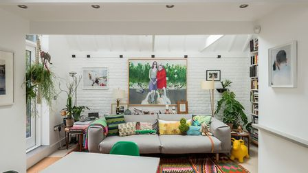 The all-white reception area is colourfully decorated by way of vibrant soft furnishings which give