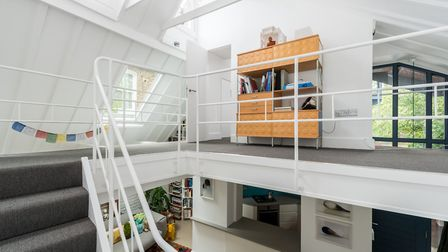 Upstairs, a walkway leads to the contemporary master bedroom as light floods in from the rooflights