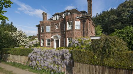 The home is shrouded in wisteria framing the walled gardens