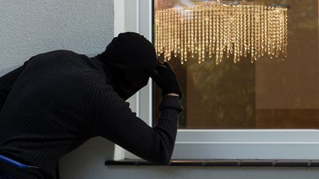 A burglar attempting to break into a property through a window. PA Photo/thinkstockphotos