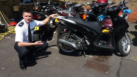 Superintendent Mark Payne with a stolen motorbike which is being dusted for fingerprints. Photo: Ann