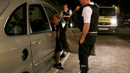 Police officer Charlie asks a man found sleeping in his car to step out of the vehicle. Photo: Cathe