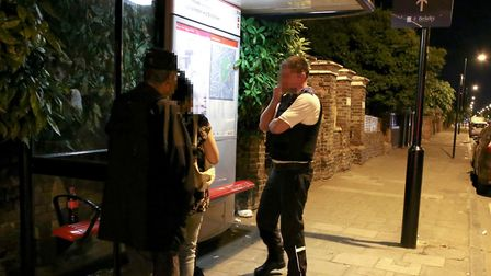 Police officer Charlie talks to people lingering at a bus stop. Photo: Catherine Davison