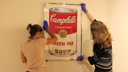 Curators at Hackney Museum hang up the Warhol print, on loan from the British Museum