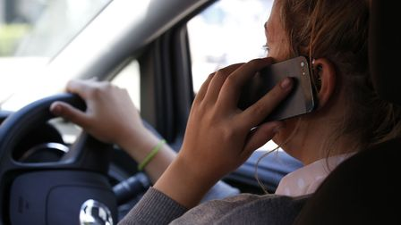 A driver using a mobile phone. PICTURE POSED BY MODEL. Photo: Jonathan Brady/PA Wire