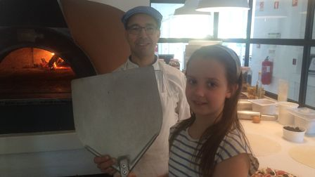 Ines with chef Gustavo in the A Terra kitchen, about to put her pizza in the wood-fire oven. Photo: