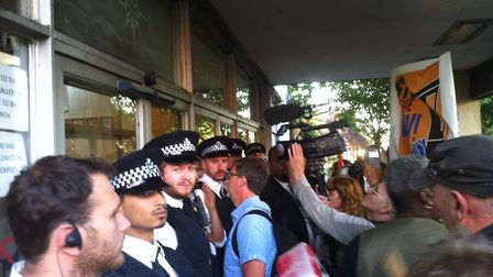 Police and security guards bar the entrance to Haringey Civic Centre in Wood Green as councillors me