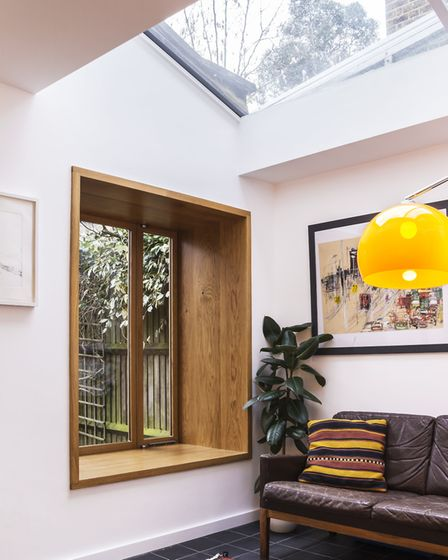 The oriel window seat is surrounded by oak and set under a skylight which floods the extension with