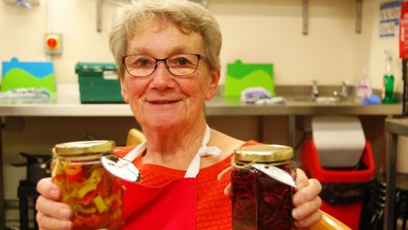 An adult family carer proudly displays finished preserves at a previous Around the Table workshop. P