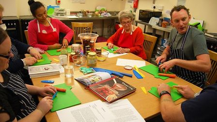Artist Kasia Posen and chef Sam Harrison work with adult family carers at a previous Around the Tabl