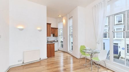 The first floor flat features floor to ceiling sash windows and high ceilings