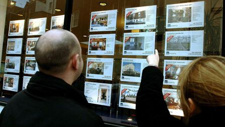 A young couple studying property for sale in an estate agent's window in central London.