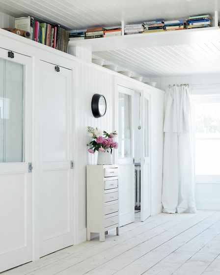 Chic white: Old books and vintage mixing bowls are displayed on high shelves in a light and airy hal