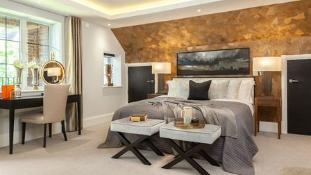 A gold faceted accent wall above the master bed adds a touch of gilt edged glamour