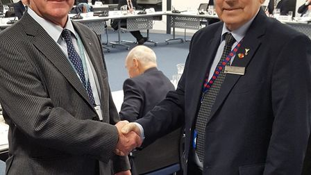 Suffolk Coastal leader Ray Herring and Waveney leader Colin Law shake hands after both district coun