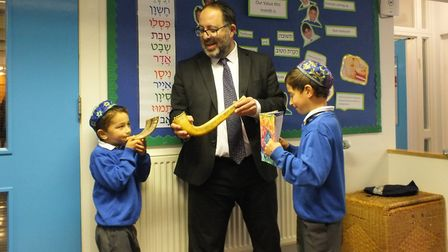 Rabbi David Mason showing students at Simon Marks Jewish Primary School how to use a shofar, or ram'