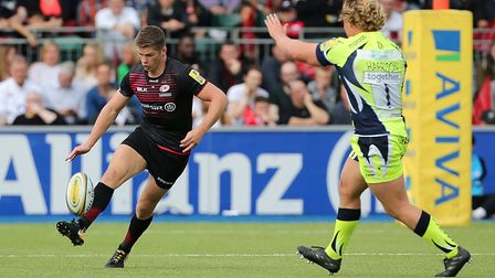 Saracens' Owen Farrell kicks forward as Sale Sharks' Ross Harrison looks to block (pic Mark Kerton/P