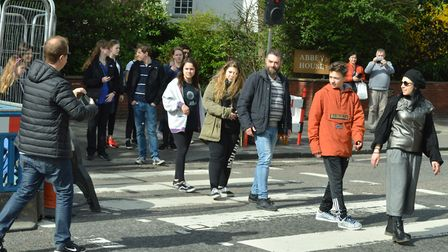Tourists pose on the Abbey Road crossing