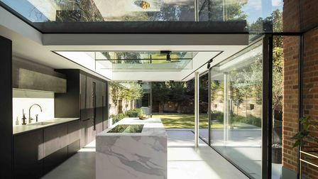 The extension is built almost entirely of glass and is topped with a floating, marble-clad canopy