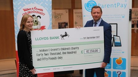Clint Wilson giving the cheque to Helen Haskell of Wallace & Gromit's Children's Charity.