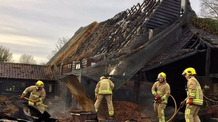 Firefighters from Wrentham damping down and checking for hotspots after a thatched house blaze in Ch