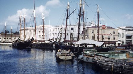 Sailing ships, known as schooners, and barges moored in the Careenage, the main harbour in Bridgetow