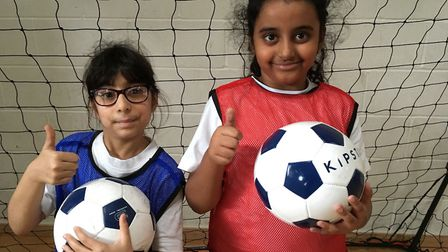 Year 3 pupils Zaynah Sultan and Ayesha Najam give the thumbs up to Olive School's girls� football pl