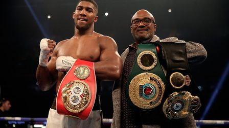 Anthony Joshua celebrates victory over Carlos Takam with his father Robert after the IBF World Heavy