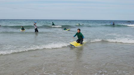 Jadine from Breakers Surf School gives encouragement as Ines catches a wave. Picture: Emma Bartholom