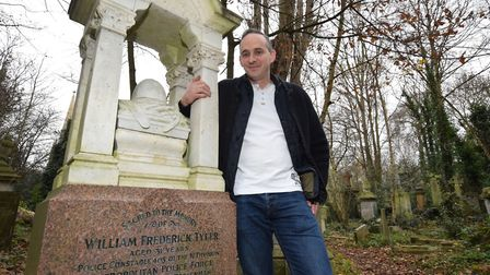 Pc Clifford Fox with the memorial to Pc Tyler at Abney Park Cemetery. Picture: Polly Hancock