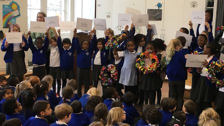 Children at Queensbridge Primary School holding up wreaths and posters commorating members of the La