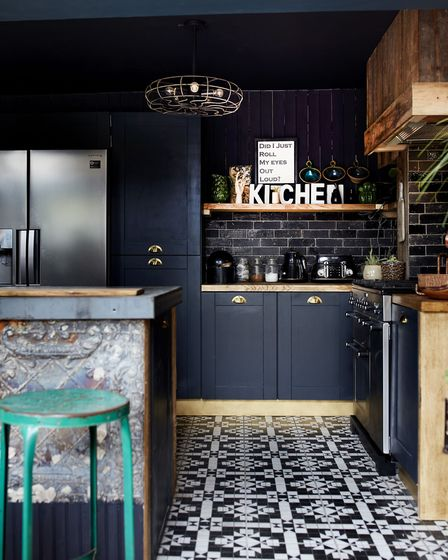 A kitchen with tin tiles, a wood-clad wall, black metro tiles and an encaustic tile floor, at the ho
