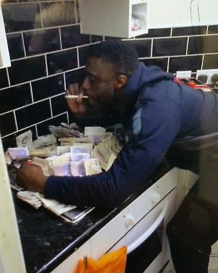 Tunji Owati posing with cash in a picture found on a mobile phone. Picture: Essex Police