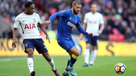AFC Wimbledon's George Francomb (right) and Tottenham Hotspur's Kyle Walker-Peters battle for the ba
