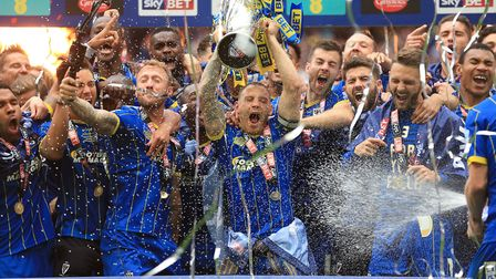 AFC Wimbledon captain Barry Fuller (centre) and his team-mates celebrate winning the League Two play