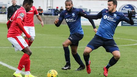 Wingate & Finchley's Ahmet Rifat looks to tackle a Harlow Town opponent with team-mate Marc Charles-