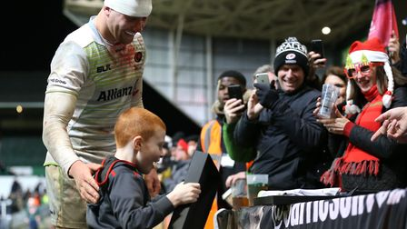 A young fan receives a Christmas present from Saracens' Nick Isiekwe (pic: Nigel French/PA)