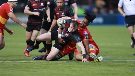 Nick Tompkins of Saracens is tackled by Max Williams of Dragons during the Anglo-Welsh Cup clash (pi
