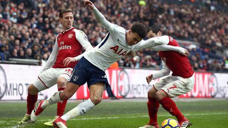 Tottenham Hotspur's Dele Alli (centre) battles for the ball with Arsenal's Nacho Monreal (left) and