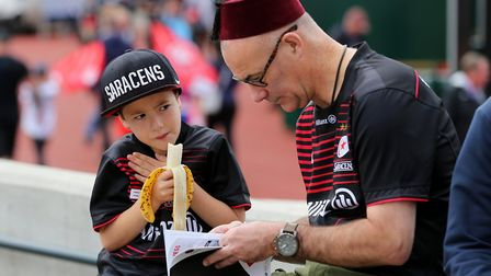 Saracens fans grab a bite to eat and read the programme before the start of play (pic Mark Kerton/PA