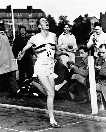 Roger Bannister breaks the tape as excited onlookers check their watches to find that Bannister has