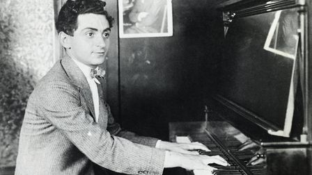 Composer Irving Berlin is shown seated at a piano, playing. Picture: George Rinhart/Corbis via Getty